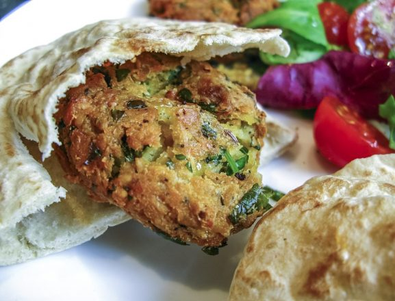 Israeli cuisine - falafel in a pita with some veggies on the side.