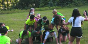 Green Team members work to build a human pyramid.
