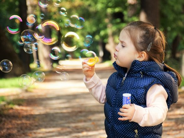 little girl blowing bubbles in a park