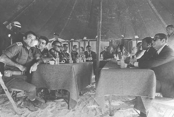 the first Egyptian-Israeli Military Talks between Israeli and Egyptian Generals at the end of the October War. Soldiers and other men sit beneath a canopy at cloth-covered tables.