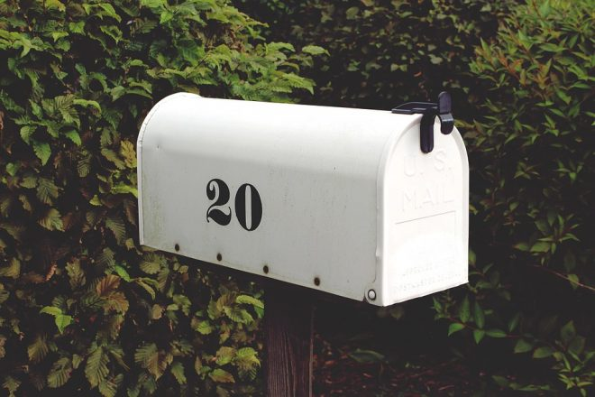 "a mailbox with the number ""20"" on it in front of some greenery"