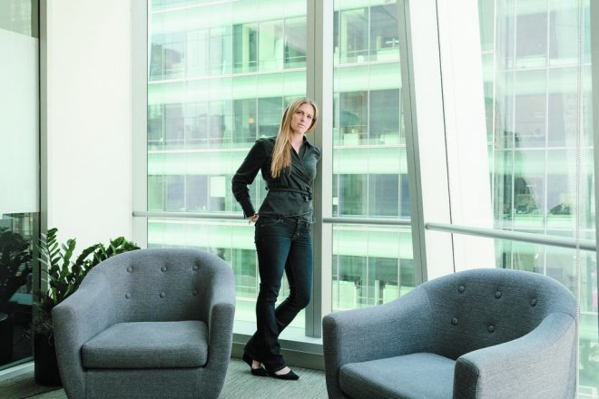 Jessica Alter, Tech For Campaigns entrepreneur, leans against a window in a large office with two large chairs in front of her.