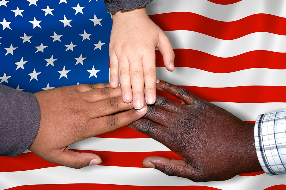American flag with three hands of different skin types meeting gin the center to show diversity.