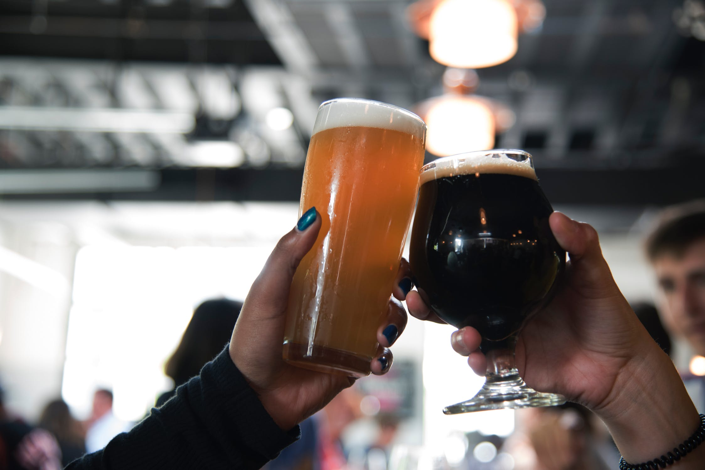 two hands raising and clinking beer-filled glasses in a toast.