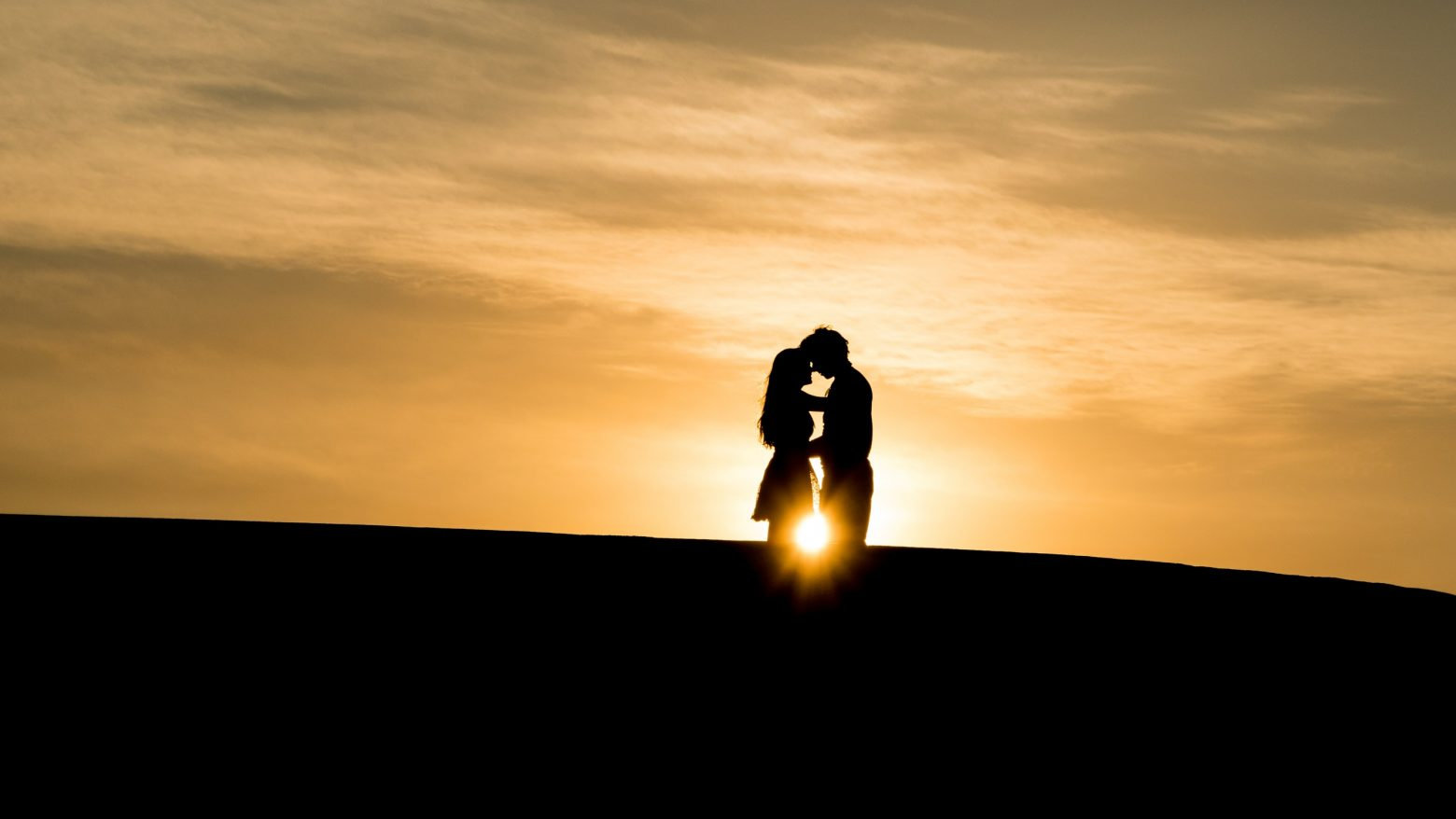 A man and woman couple stand silhouetted in front of a sunset at golden hour.