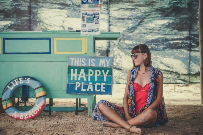 "girl sits on a beach beside a sign that says ""this is my happy place"" and a life preserver that says ""life's a beach"""