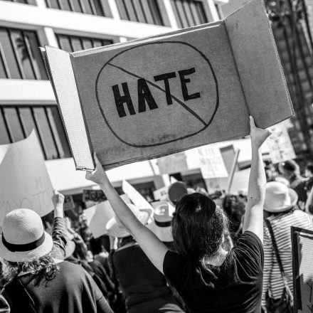"woman holding up a sign at a protest viewed from the back. The sign reads ""HATE"" with a circle and a slash around it to say no hate"