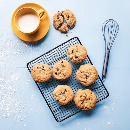chocolate chip cookies cool on a wire rack next to a mug full of milk and a whisk.