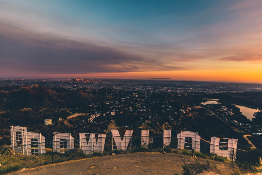 A view from behind the Hollywood sign of Los Angeles at sunset.