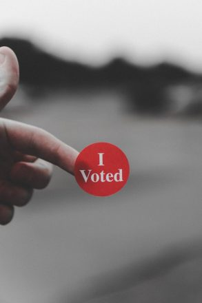 """hand holding out a sticker that reads """" I voted"""""""