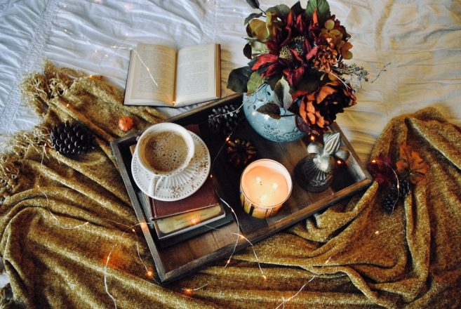 open book and a tray with tea and flowers and a lit candle with some fairy lights around it on a blanket on a bed.