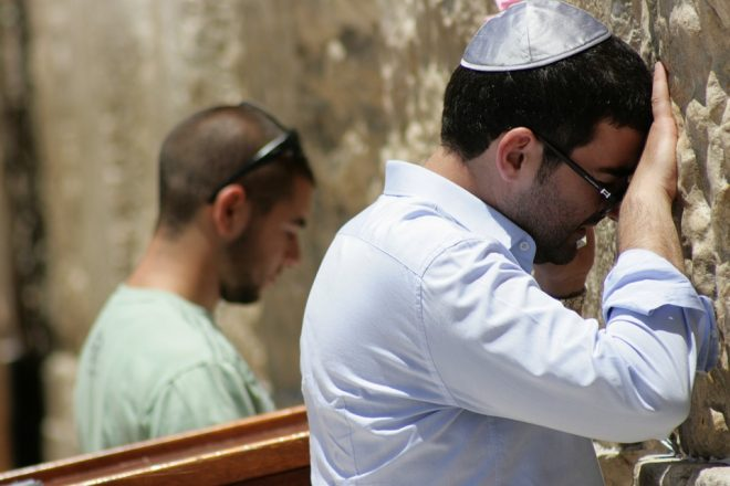two men praying at the Western Wall in Jerusalem