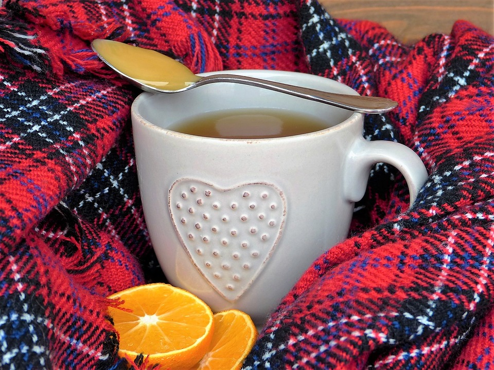 cup of tea with a spoon of honey resting on the cup and two orange slices next to it. There is a plaid or gingham scarf or blanket around the cup and the cup has a heart on it.