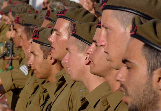 male soldiers stand in a row in uniform. Close-up on their faces.