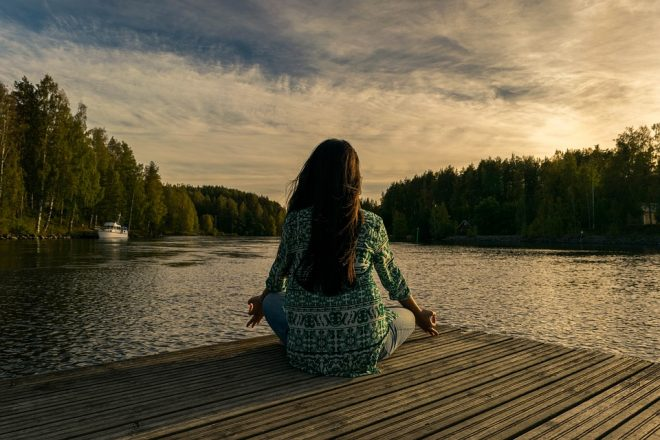 yogi woman practicing meditation on a dock by a body of water surrounded by trees
