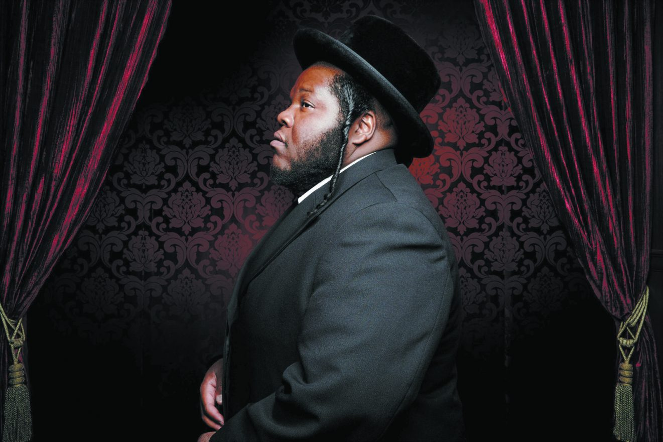Rapper Nissim Black, a black man with curled pais and a black top hat and suit stands in profile before a velvet curtain and intricately designed wallpaper.