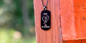 "A black necklace tag with a heart and the words ""Family. DNA not required"""