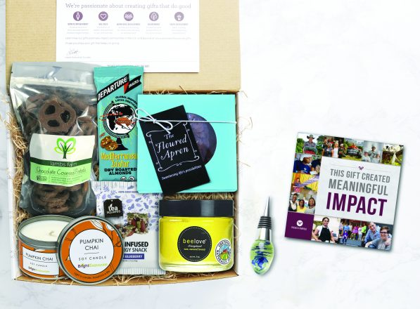 "Packed with Purpose gift with different foods like chocolate covered pretzels and candles, a bottle stopper, and a card that reads ""this gift created meaningful impact"""