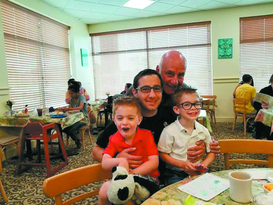 LEFT TO RIGHT: Ori Glaser, 5, Craig Glaser, Joe Stuban and Yoav Glaser, 6. Family smiles anbd poses together in a classroom