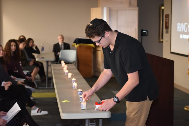 Tenth-grader Daniel Lerman of Southfield lights a candle for Pittsburgh shooting victim Irving Younger.