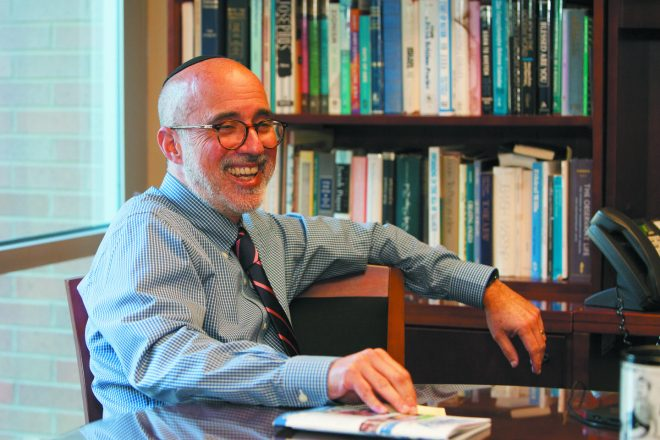 Steve Freedman, white man with glasses and a beard in a dress shirt and tie, sits at a table with a full bookshelf behind him as he smiles to something off in the distance. He is wearing a kippah.