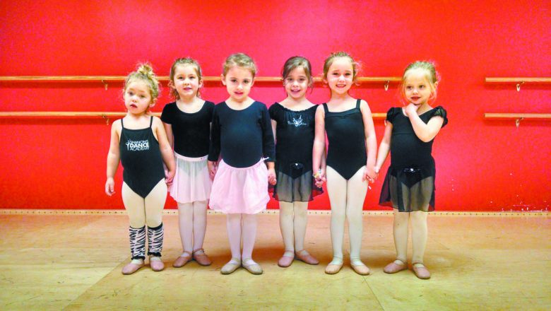 six little girls in stand in a row facing the camera wearing leotards with dance skirts and ballet slippers.