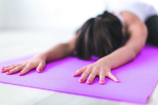 a woman doing yoga on a yoga mat. She is laying with her head down and her arms outstretched.