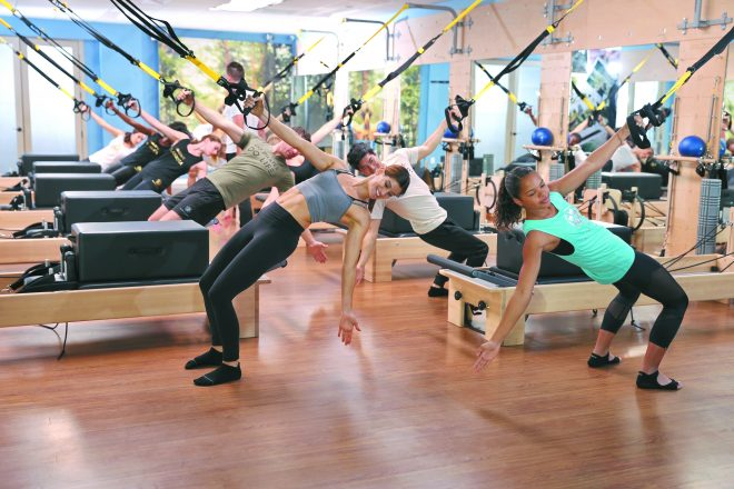 a bunch of women and men doing pilates in a gym