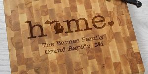 "cutting board that says ""home."" with the ""o"" as the print of the state of Michiigan. Beneath it reads ""The Barness Family. Grand Rapids, MI"""