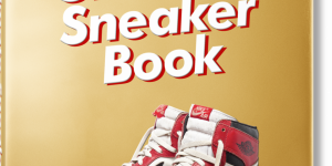 The front cover of the book The Ultimate Sneaker Book with a gold jacket and red and white nike shoes on the front
