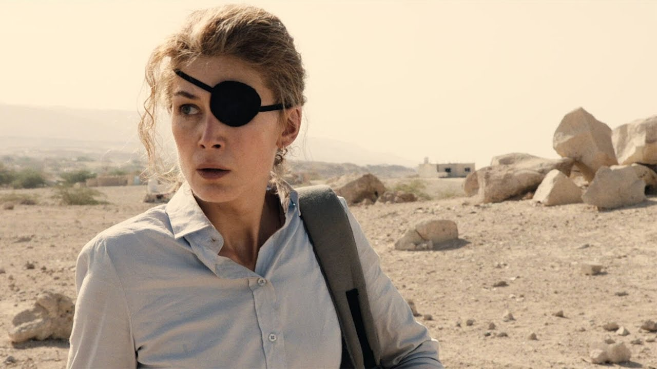 Rosamund Pike as war journalist Marie Colvin seen with an eye patch in a mountainous desert area in a still from the movie A Private War