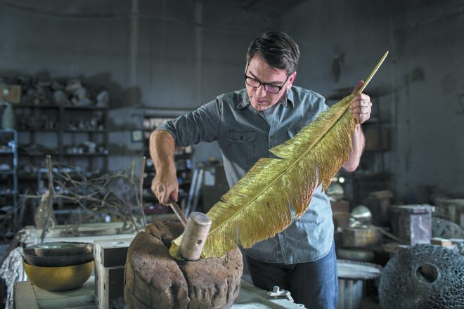 "Michael Aram at work, creating ""perfectly imperfect"" organic-inspired pieces, which he calls a reflection of our humanity. This one is a giant golden feather that he is holding up and hammering with a rubber or wooden hammer."