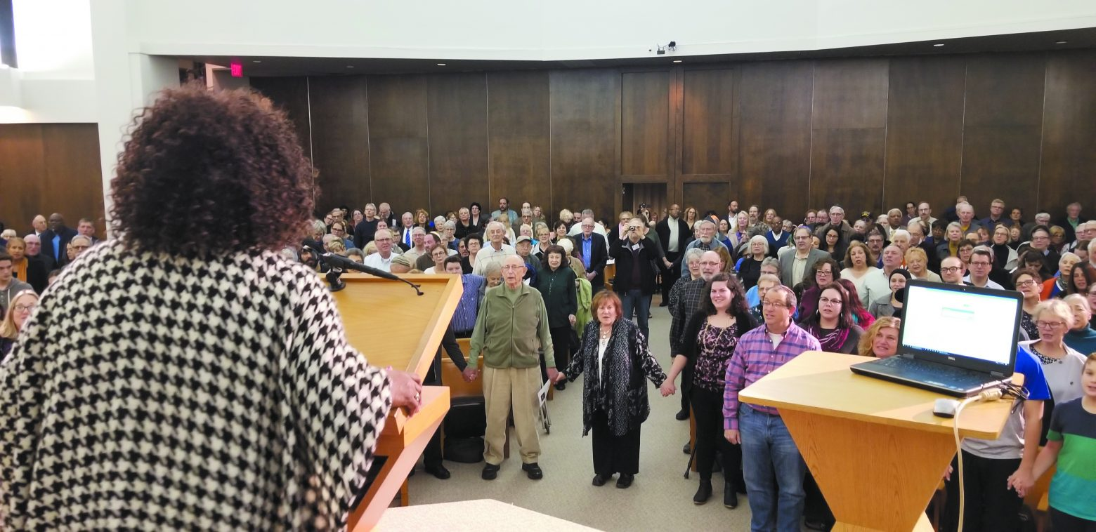 "Chaplain Yvonne Fant Moore leads the singing of ""We Shall Overcome"" at the interfaith service at Beth Shalom in Oak Park."