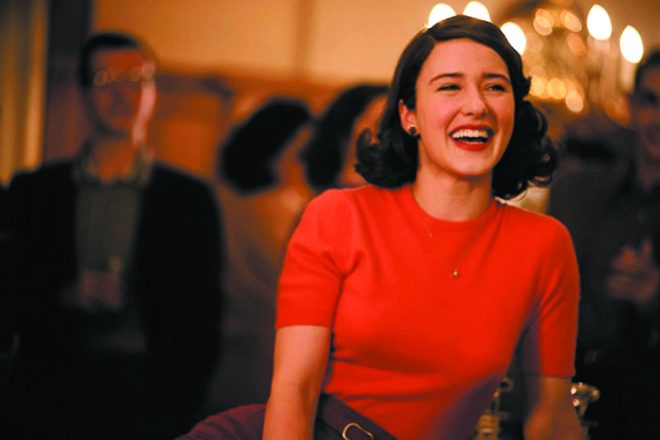 Rachel Brosnahan as Midge Maisel, a white Jewish woman with shoulder-length hair and a bright red, tight dress. Maisel is smiling in the photo.