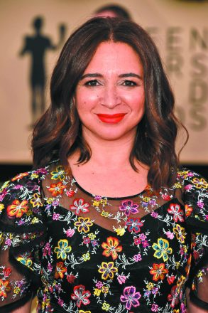 Maya Rudolph smiles at the camera with lightly curled hair and a flower-print dress.