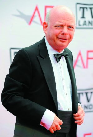 Wallace Shawn, a bald white man in a tuxedo