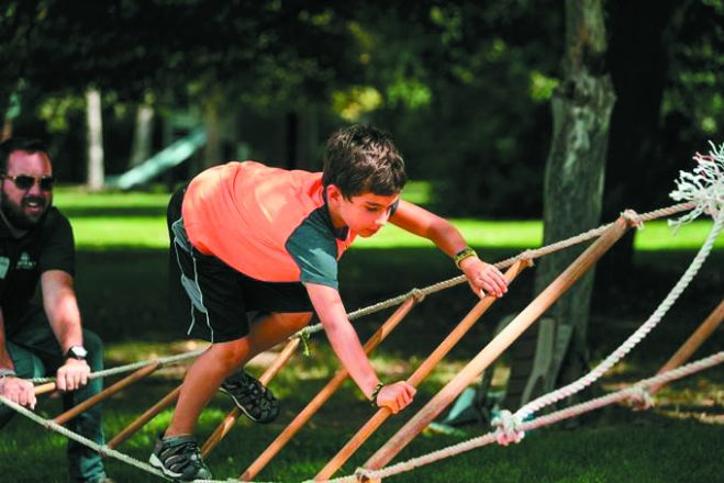 Camp Hermelin attendee balances on Jacob's Ladder.