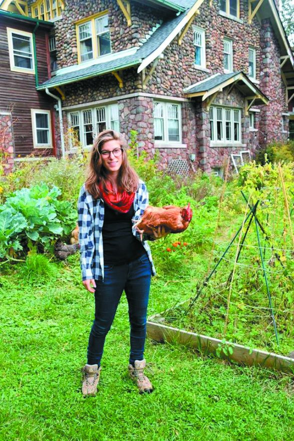 Carly Sugar and one of the chickens she raises in her Detroit backyard.
