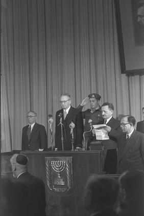 Knesset Speaker Joseph Sprinzak swears in Yitzhak Ben-Zvi as president on Dec. 10, 1952. He stands at an alter with a menorah on a tapestry on it and a soldier soluting behind him while men gather around and watch.