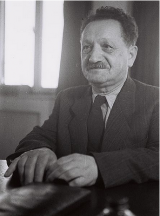 Joseph Sprinzak, a man in a suit with a mustache, sits at a table playing with his hands and staring off into the distance.