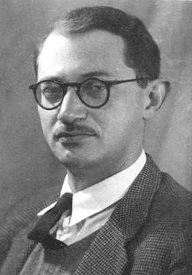 Shmuel Katz headshot with a man in a suit and glasses.