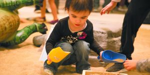 A little girl with brown hair, Ma'ayan Bernhardt, 2, of West Bloomfield digs in the sand for dinosaurs.