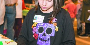 A girl with brown shoulder-length hair and a shirt with a sugar skull on it, Naamah Rosenzweig, 9, of West Bloomfield crafts at a table