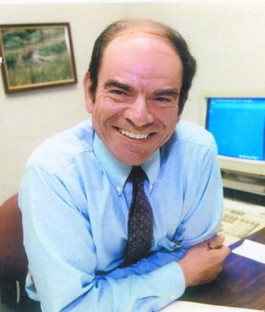 Berl Falbaum sits and smiles at his desk wearing a dress shirt and tie