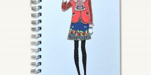 "Notebook with an illustrated fashionista that says ""wear on my gucci notebook"". The illustrated girl has her hand up with a scout's honor type sign."
