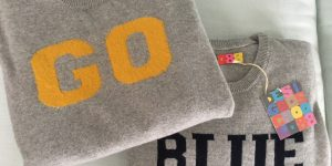 "two sweaters that read ""GO"" and ""BLUE"" on them."