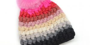 a chunk-block colored hat with stripes and a large pouf on the top. Winter hat.