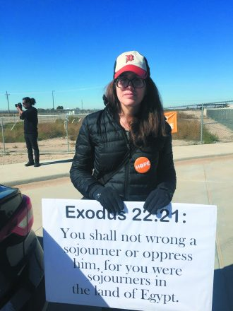 "Rachel Goldberg stands with a Detroit Tigers hat, a button that reads ""HOPE"" and a sign that says ""Exodus 22:21: You shall not wrong a sojourner or oppress him, for you were sojourners in the land of Egypt."""
