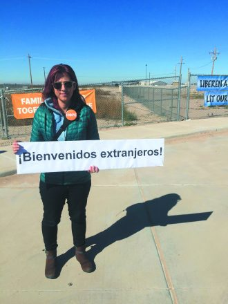 "Wendy Lawrence stands with sunglasses on with a pin that says ""HOPE"" and a sign that reads, ""¡Bienvenidos extranjeros!"""