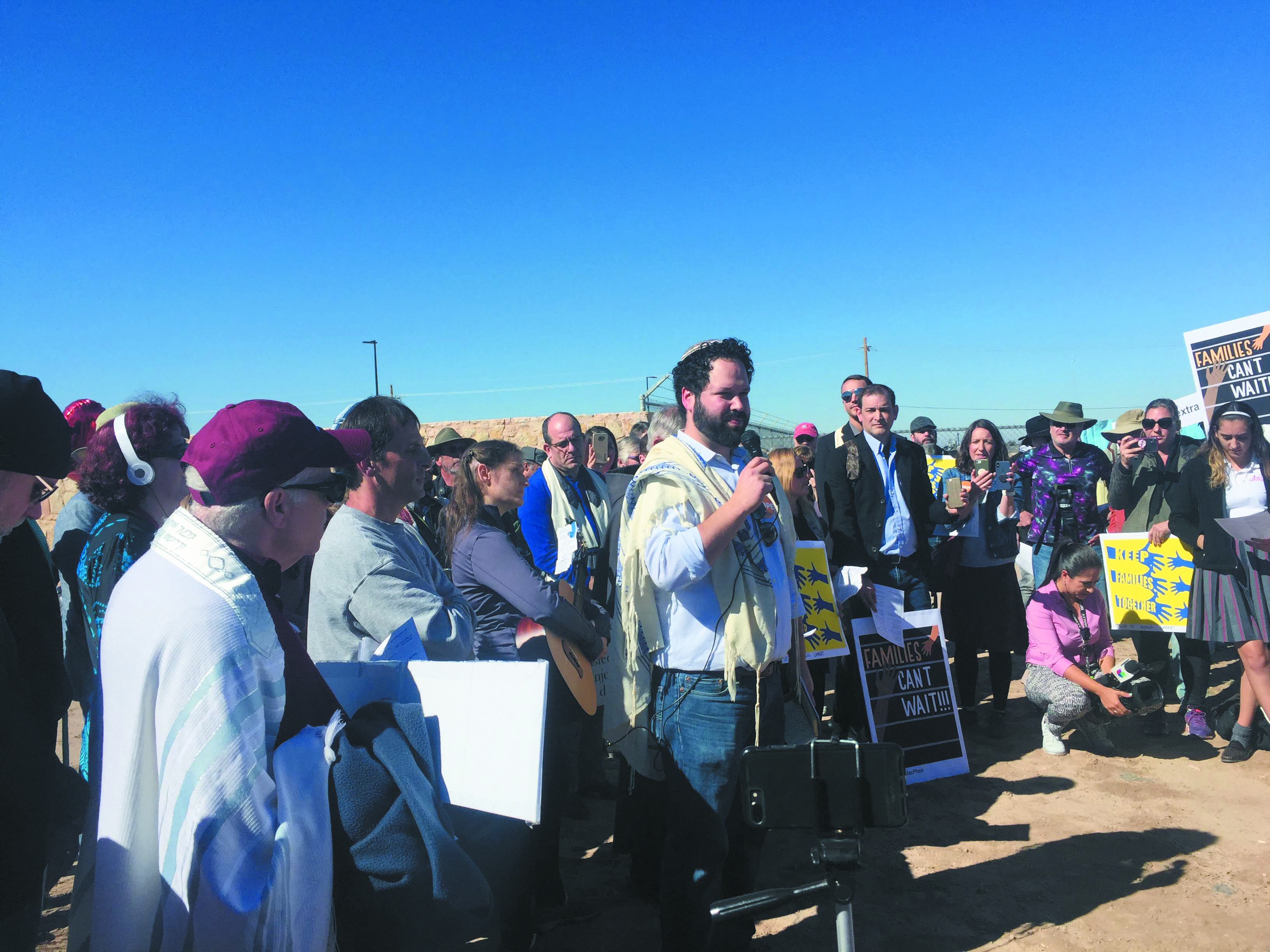 Rabbi Josh Whinston of Temple Beth Emeth in Ann Arbor speaks to a multi-faith group protesting outside the Tornillo, Texas, detention center. He is in the center standing in a tallit and kippah while people with signs stand around him and watch and listen.